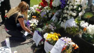 Mujer coloca flores en homenaje a los fallecidos en el naufragio