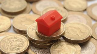 A plastic model of a house on a pile of one pound coins