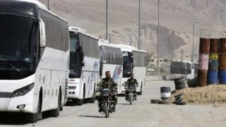 Syrian government forces drive motorbikes past buses waiting at the entrance of Harasta in the rebel-held Eastern Ghouta (22 March 2018)