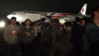 Passengers stand outside the plane