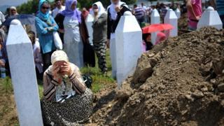 Srebrenitsa'da yakınını kaybeden bir Boşnak mezar başında ağlıyor