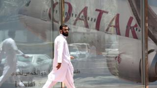 Man walking past window with reflection of Qatar Airways plane in Riyadh, 6 June