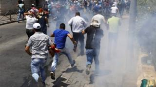 Palestinians run after stun grenades are fired outside Jerusalem's Old City (28/07/17)