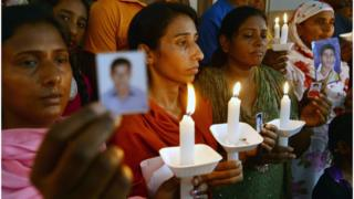 نساء يقفن بشموع مضاءة