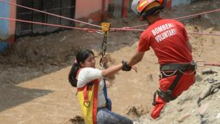 Спасатели помогают девушке в Лиме