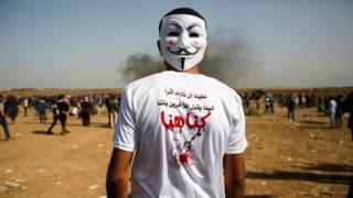 """صورة لمتظاهر فلسطيني يرتدي قميص كُتب عليه """"علينا أن نترك أثرا شيئا يقول للاخرين بأننا كنا هنا""""، في يوم جمعة الكاوتشوك في السادس من أبريل/نيسان 2018"""