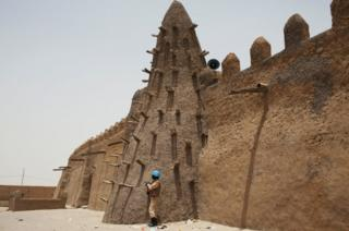 A UN peacekeeper from Burkina Faso stands guard at the 14th Century Djinguereber mosque in Timbuktu, Mali