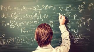 Maths teacher writes on board (library image)