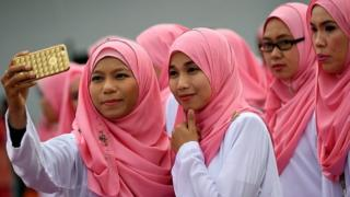 Members of the ruling party United Malays National Organisation (UMNO) pose for photographs before the opening ceremony of the party's annual congress in Kuala Lumpur on December 1, 2016.