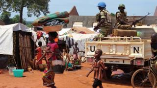 A woman and a child walk past UN peacekeepers from Gabon patrolling the Central African Republic town of Bria on June 12, 2017