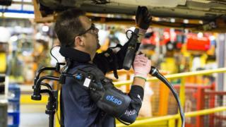 A car worker using a robotic suit
