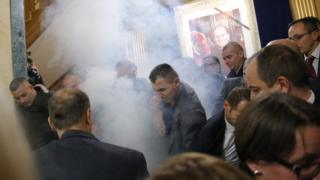 Opposition MPs throw tear gas as Kosovo police officers stop them from attending a continuing session of the parliament in Pristina