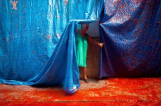 A resident of Bunol, near Valencia in Spain, pulls back the protective sheeting during the annual Tomatina festival