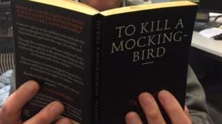 A man reads To Kill a Mockingbird novel. File photo