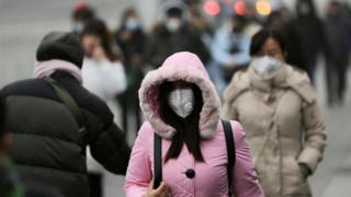 12月21日,北京街頭,一處辦公區域附近戴口罩的行人。