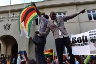People wave national flags as they celebrate outside the parliament in Harare, after the resignation of Zimbabwe's president Robert Mugabe on November 21, 2017.
