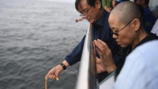 Liu Xiaobo's wife Liu Xia (R) prays as his ashes are scattered in the sea near Dalian