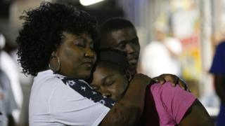 Mourners embrace during a vigil