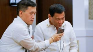 Filipino President Rodrigo Duterte (R), assisted by Special Assistant to the President Christopher Lawrence Go (L), speaking to US President Donald J. Trump during a phone call on the sidelines of the gala dinner