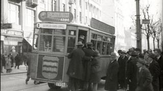Putnici pokušavaju da se popnu u pun tranvaj, scena iz filma