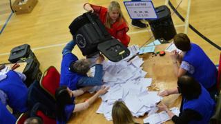 Election count staff empty a ballot box