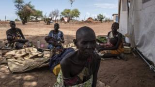 A cholera-stricken woman showing signs of malnutrition sits next to fellow patients (background) outside a temporary field hospital near the remote village of Dor within the Awerial county in south-central Sudan on April 28, 2017