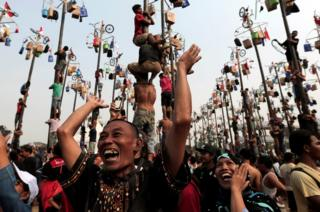 A couple reacts as their colleague wins a bicycle during greased pole competition during the celebration of Independence Day at Ancol Dreamland Park in Jakarta, Indonesia