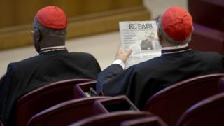 A cardinal attending the Synod on the Family reads a newspaper showing a picture of gay bishop Krzysztof Charamsa and his partner Eduard before the start of the morning session (09 October 2015)