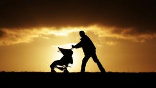 A man pushing a baby buggy during sunset on Parliament Hill