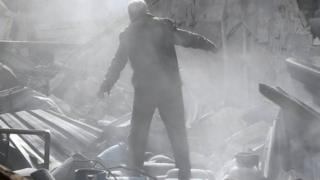 A man stands on the rubble of damaged buildings after an air strike on the rebel-held town of Mesraba in Eastern Ghouta, Syria. Photo: 26 November 2017