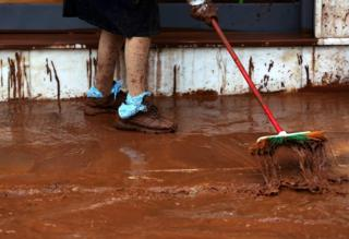 A woman sweeps mud outside her house.