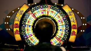 A man tries his luck at a wheel of fortune machine