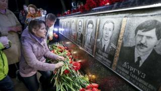 事故の犠牲となった原発従業員や消防隊員の記念碑に花を捧げる人々(26日、ウクライナ・スラブティチで)