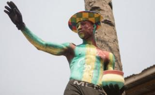 """A Togolese man with body paint in the colours of the national flag and the letter C92 referring to the return to the 1992 Constitution in Togo and for the departure of the current president, watch a protest rally by women marching against Togo""""s president in the capital Lome on January 20, 2018."""