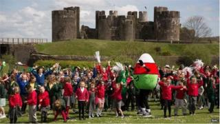 Caerphilly Castle with Mr Urdd mascot and children