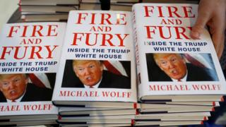 "A shop worker arranges copies of Michael Wolff""s book ""Fire And Fury"" as they go on sale inside a branch of the Waterstones book store in Liverpool, Britain"