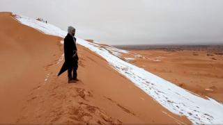A man looks at at a snow-covered slope in the Sahara, Ain Sefra, Algeria, January 7, 2018 in this picture obtained from social media.