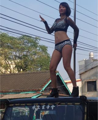 This picture taken on 3 January 2017 shows a pole dancer performing on top of a jeep during the funeral procession of former Chiayi City county council speaker Tung Hsiang in Chiayi City, southern Taiwan.