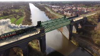 A CGI image of the proposed cycle and walk path alongside a train on the Cadishead viaduct