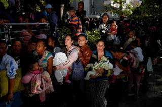 Women carrying babies queue as they try to buy nappies outside a pharmacy in Caracas, Venezuela, on 18 March 2017.