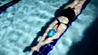 A file photograph shows a woman swimming underwater in a swimming pool