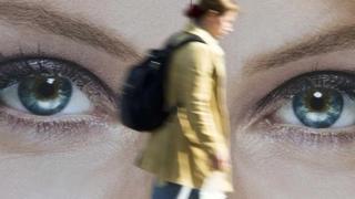 Una persona caminando frente a una imagen de unos ojos gigantes
