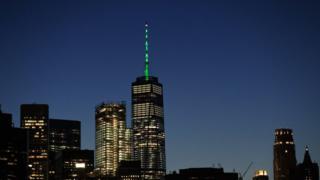 One World Trade Center glowing green against New York skyline