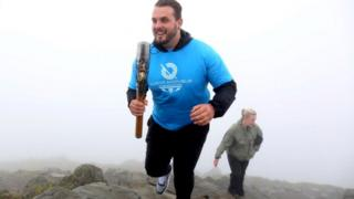 Aled Sion carrying the Queen's Baton up Snowdon