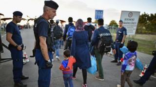 Migrants arrive at a border point between Croatia and Hungary where they will be transported by bus through to Austria on September 21, 2015