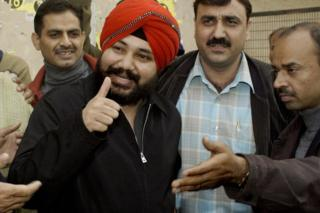 Daler Mehndi gestures at photographers as he arrives at a Delhi court on 20 December 2003.
