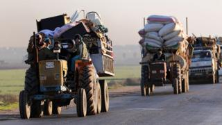 Displaced Syrians travel along a road near the rebel-held town of Saraqeb in Idlib province (7 January 2018)