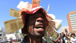 A protester wearing a hat with old Zimbabwe dollar notes attached to it in Harare - Wednesday 3 August 2016