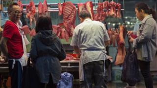 Pessoas compram carne em açougue em Hong Kong