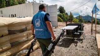 Funcionarios de la ONU con armas entregadas por las FARC